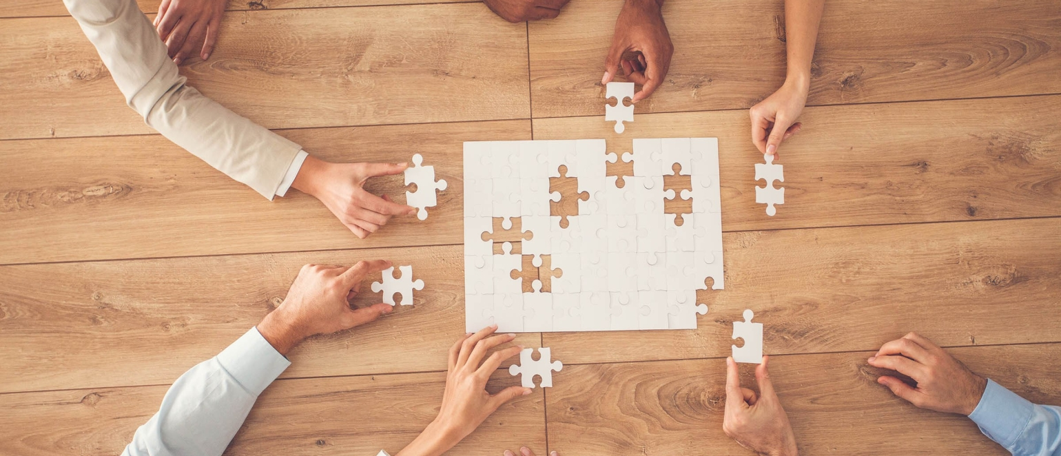 Business people sitting at office desk, putting puzzle pieces together, finding solution, high angle view.